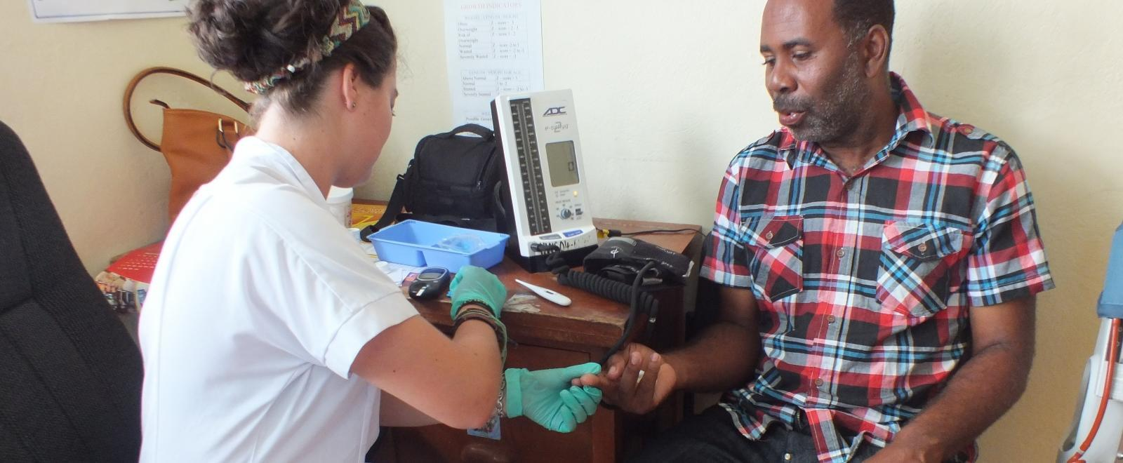 A student doing her medical elective abroad checks blood sugar levels during a community outreach.